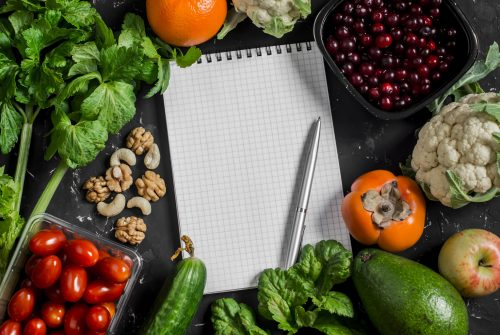 Food background. Fresh vegetables, fruits and blank notepad on a dark background. Concept of healthy eating, diet and planning